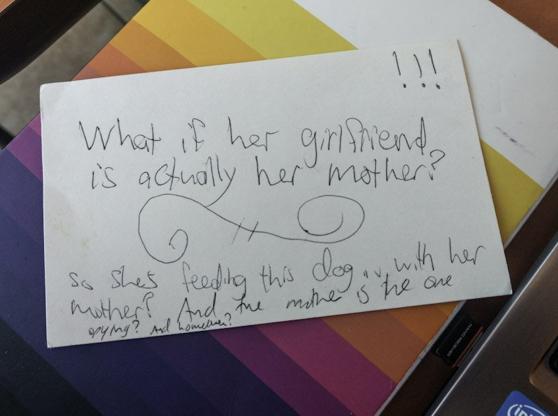 "An index card with ""What if her girlfriend is actually her mother?"" written on it in shaky, slanted handwriting."