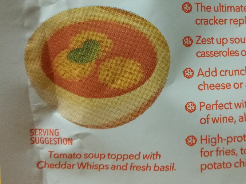 Serving suggestion for tomato soup topped with Cheddar Whisps