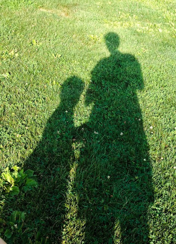 Shadows of a parent and child on the grass