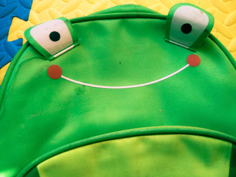 Child's backpack with rosy-cheeked smile.