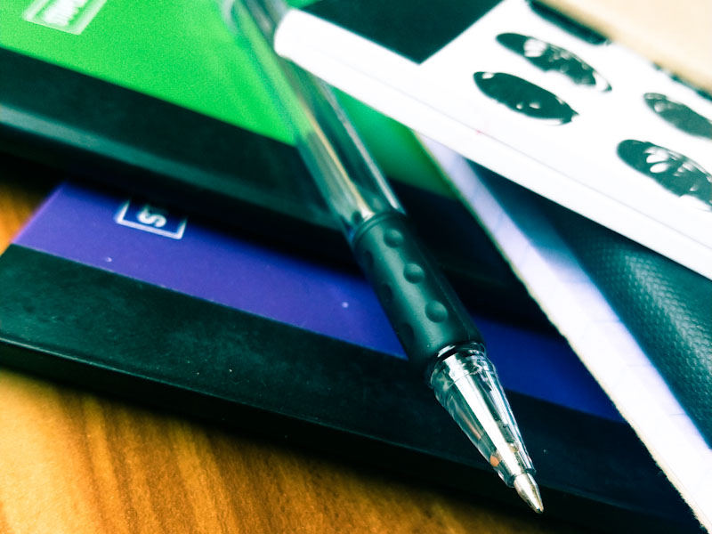 A pile of purple, green, and black composition notebooks.