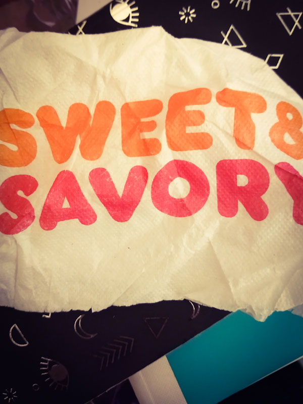"A Dunkin Donuts napkin that reads ""Sweet & Savory"""
